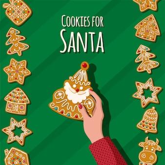 緑の背景にジンジャーブレッドサンタクロースクリスマス自家製クッキーを保持します