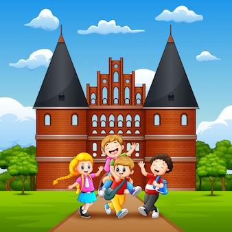 Holstentorの前で楽しいと笑っている幸せな学校の子供たち