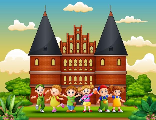 Holstentorの建物の前に立っている幸せな学校の子供たちの漫画