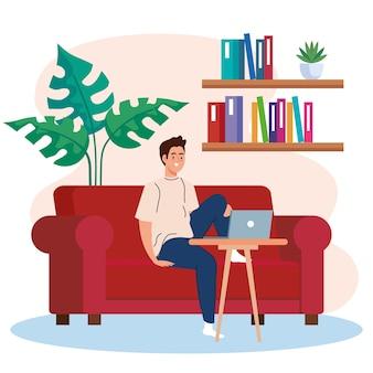 自宅の仕事、ソファの上のラップトップを持つフリーランサーの若い男、リラックスしたペース、便利な職場で自宅で仕事