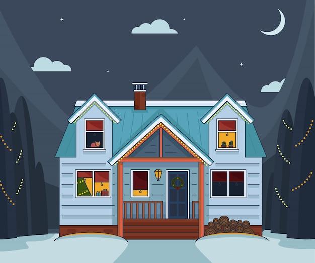 クリスマスに装飾された、窓に温かみのある黄色のライトが配された親しみやすい居心地の良いコテージ