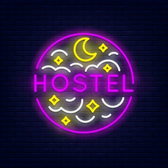 Hostel colorful neon banner at brick wall