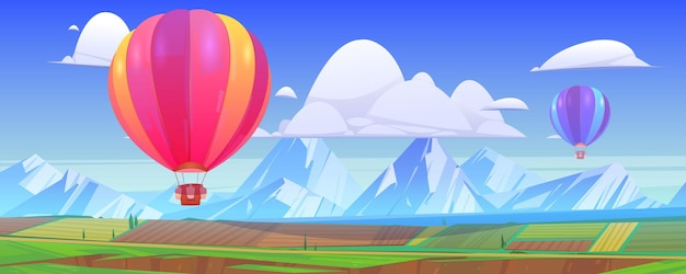 Hot air balloons fly above mountain landscape with green meadows and fields in valley.