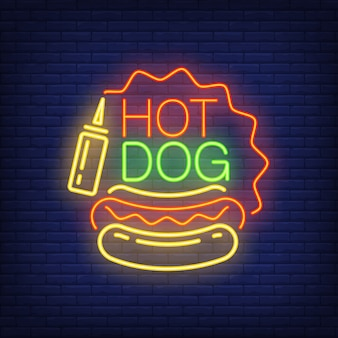 Hot dog neon sign. sausage loaf, mustard and star shaped frame on brick wall background.