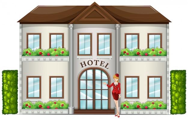 Un addetto d'albergo in piedi di fronte all'hotel