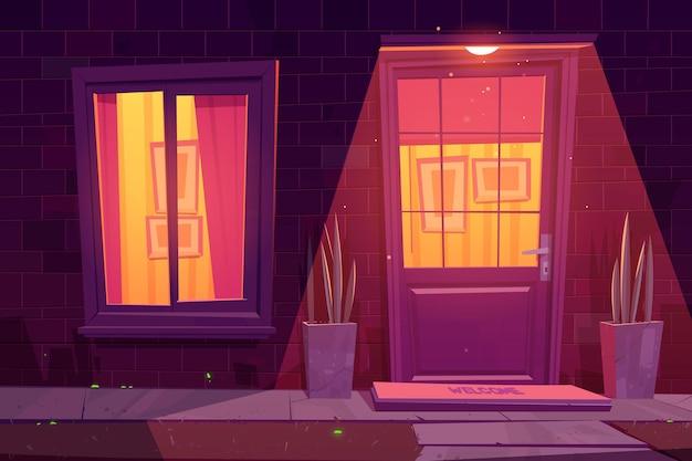 벽돌 벽, 흰색 창 및 문, 식물 및 외부 램프가있는 집 외관.