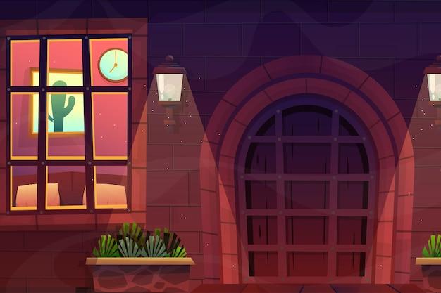 벽돌 집의 전면 나무 문이 있고 벽에 램프가 있는 집 정면은 유리창을 통해 보고 집 내부를 보았습니다.