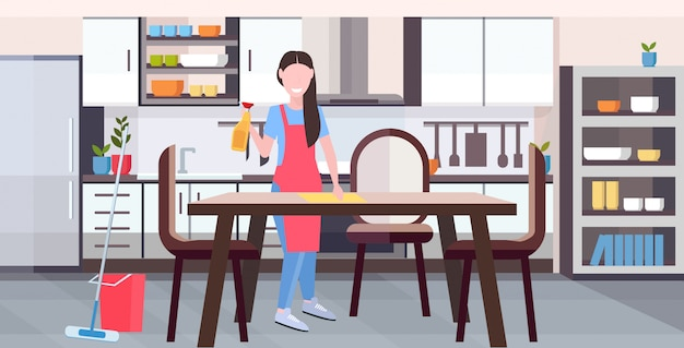 Housewife in apron wiping dinning table by dust cloth girl doing housework cleaning service housekeeping concept full length flat modern kitchen interior horizontal