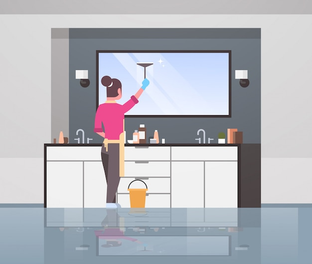 Housewife in gloves and apron cleaning mirror with squeegee woman doing housework concept modern bathroom interior rear view female cartoon character