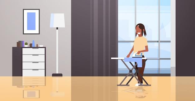主婦アイロン服女性持株鉄笑顔の女の子家事コンセプトモダンな家のリビングルームのインテリア女性漫画のキャラクター全長水平