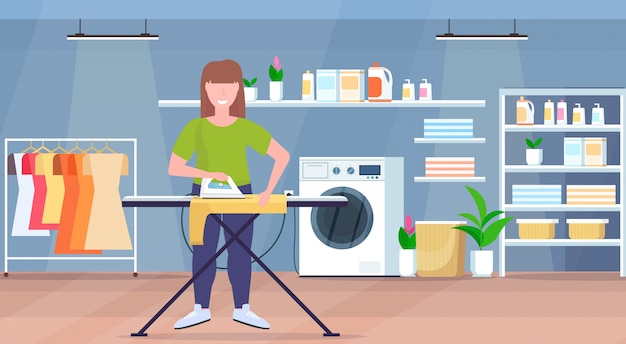Housewife ironing clothes young woman holding iron smiling girl doing housework concept modern laundry room interior female cartoon character full length flat horizontal
