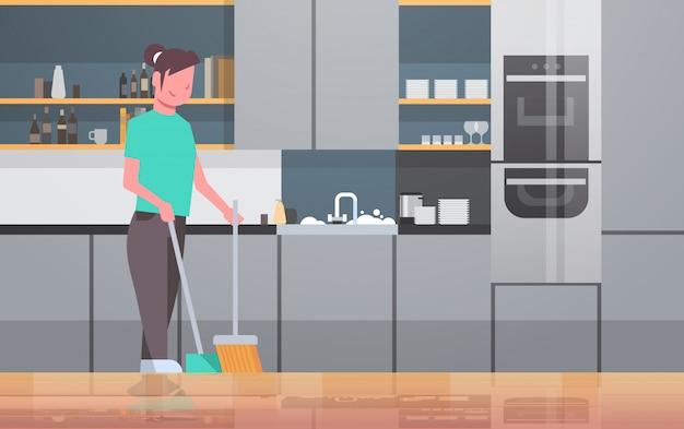 Домохозяйка подметать пол с метлой и совок молодая девушка делает по дому уборка концепция современная кухня интерьер женщина мультипликационный персонаж