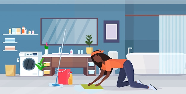 Housewife washing floor on knees african american woman cleaner using cloth and bucket girl doing housework cleaning service concept modern bathroom interior full length flat horizontal