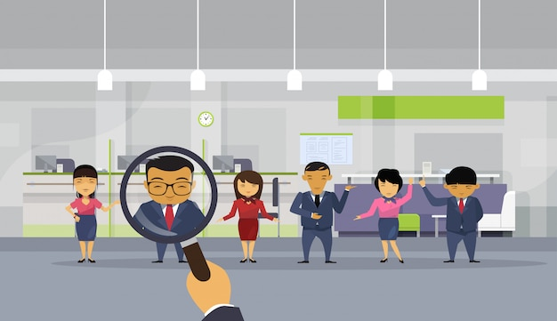 Hr hand hold magnifying glass choosing businessman from asian business people