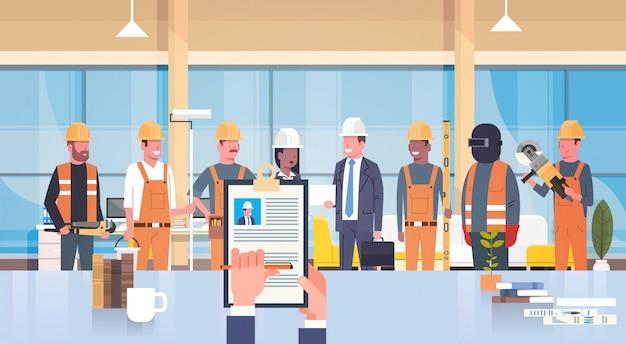 Hr manager hand hold cv резюме строителя над группой строителей выбирает кандидата на должность