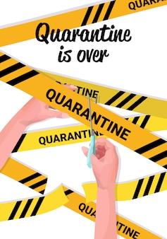 Human hand cutting yellow tape with scissors coronavirus quarantine is over covid-19 pandemic ending