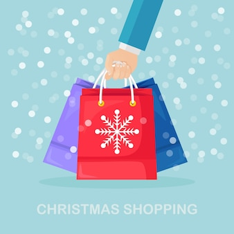 Human hand hold shopping bags with snowflakes. christmas, new year sale