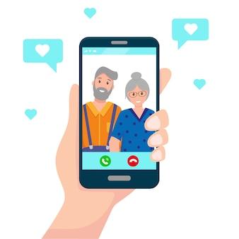 人間の手は、両親や祖父母とのオンライン通信のための画面上の幸せな老夫婦とスマートフォンを保持します。