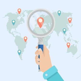 Человеческая рука держит увеличительное стекло для поиска лучшего места для путешествия на карте мира