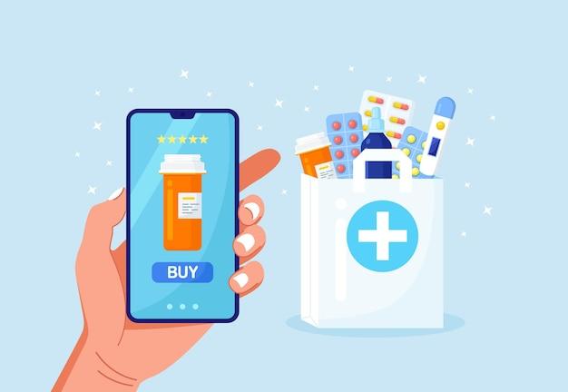 의학 온라인 지불을 위해 휴대 전화를 들고 있는 인간의 손. 택배 약국 서비스. 약병, 약, 약, 온도계가 들어 있는 종이 봉지. 의료 지원, 건강 관리 개념