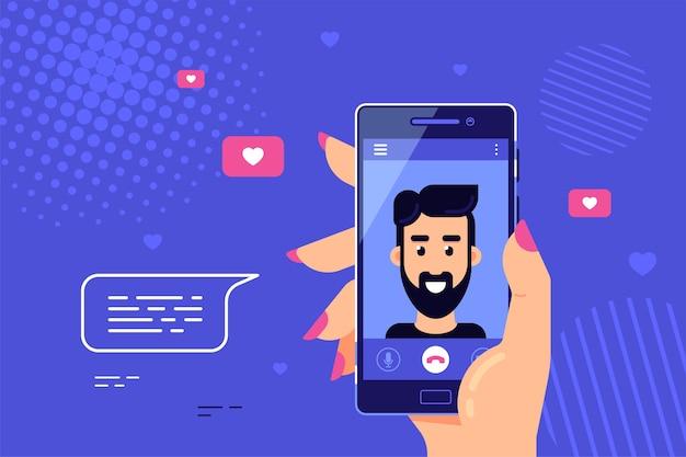 画面上の男性キャラクターとスマートフォンを持っている人間の手。ビデオ通話、オンラインビデオチャット、インターネット技術。