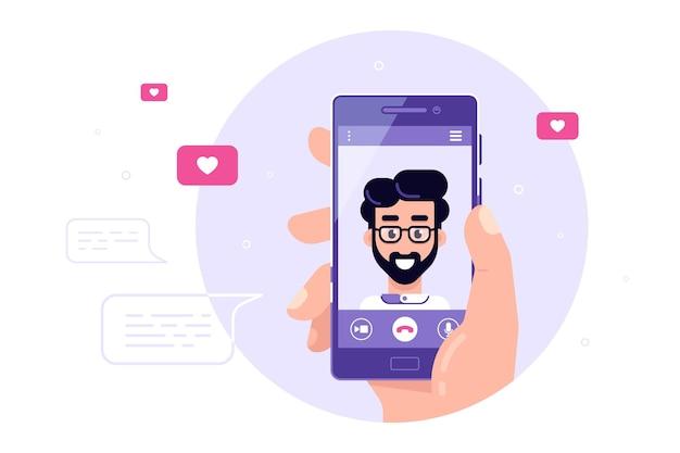 画面上の男性キャラクターとスマートフォンを保持している人間の手。ビデオ通話、オンラインビデオチャット