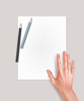 Человеческая рука над чистым листом бумаги с карандашами