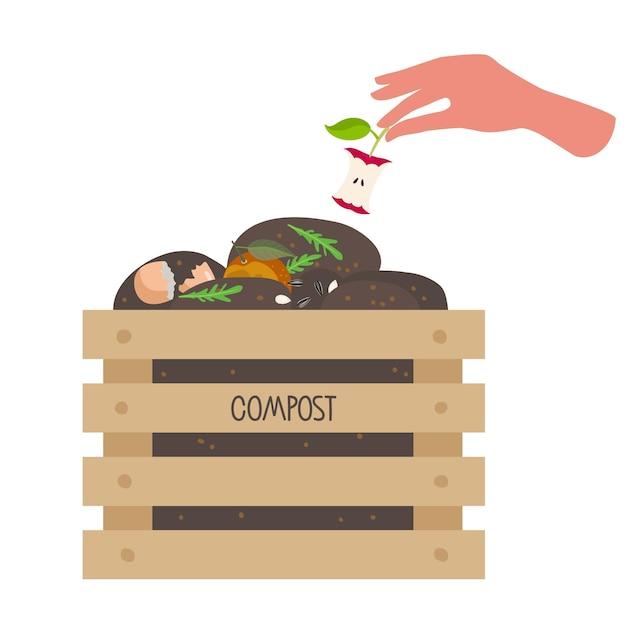 Человеческая рука кладет ядро яблока в коробку с компостом деревянный ящик с фруктами, овощами, обрезками, зеленью