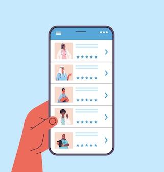 Human hand using smartphone choosing doctor in mobile app online medical consultation healthcare service medicine concept