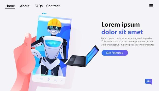 노트북 현대 로봇 캐릭터를 사용하는 헬멧에 로봇 엔지니어와 스마트 폰을 사용하는 인간의 손