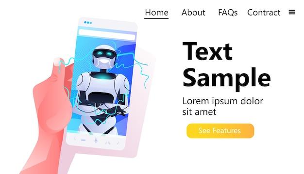 Человеческая рука с помощью смартфона с роботом на экране смартфона современный роботизированный персонаж концепция искусственного интеллекта
