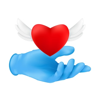 A human hand wearing blue protective surgical glove with a flying red heart with angel wings.