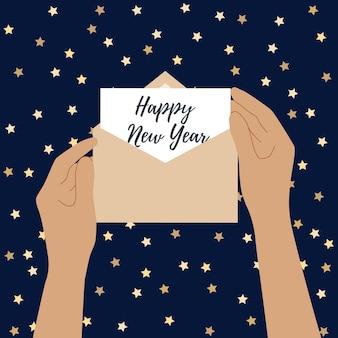人間の手は手紙で開いた封筒を持っています。明けましておめでとうございます。