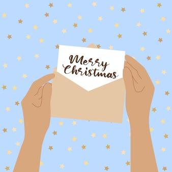 人間の手は手紙で開いた封筒を持っています。メリークリスマスおめでとうと手紙を読むの概念。グリーティングカード。ベクトルフラットイラスト