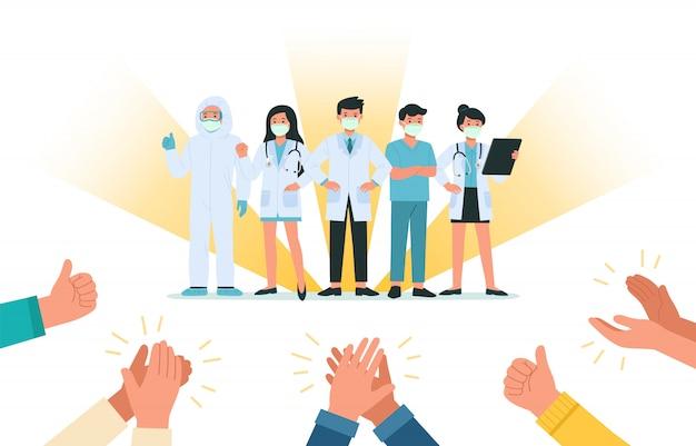フェイスマスクをつけた勇敢な医師と看護師のために手をたたく人間の手が、コロナウイルス病のコビッド19と戦う。彼らは英雄です。ヘルスケアと安全。健康細菌ウイルス保護。