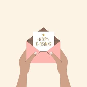人間の手は、メリークリスマスの挨拶で開いた封筒を保持します現代ベクトルイラスト
