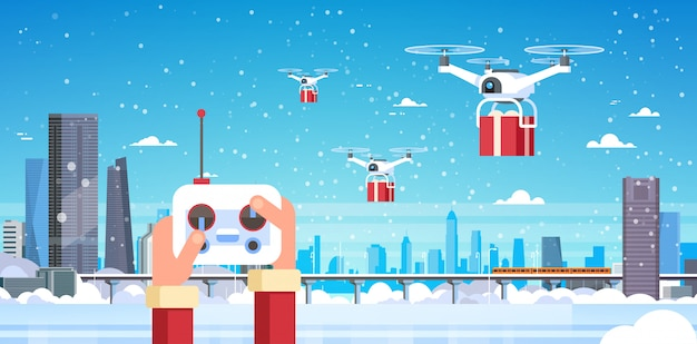 Human hands hold controller drone delivery service over modern winter city
