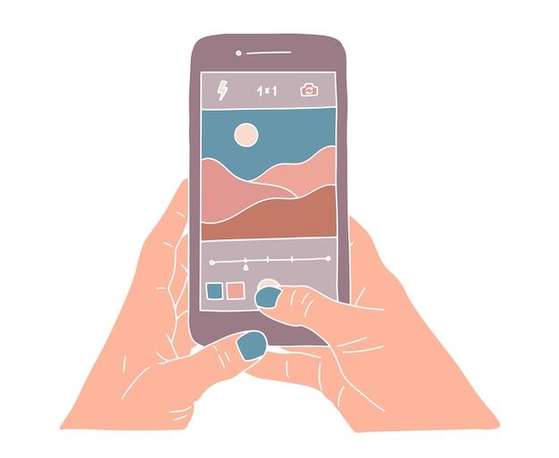 スマートフォンを持って、美しい自然の風景写真を撮る人間の手