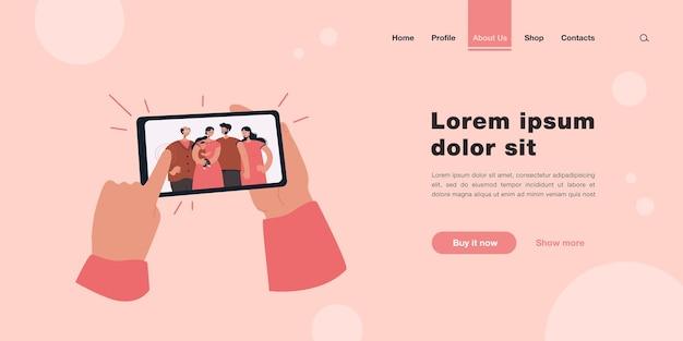 Человеческие руки держат смартфон с семейной целевой страницей селфи в плоском стиле