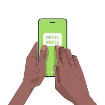 인간의 손에 스마트 폰 화면에서 해독 모드를 눌러 디지털 해독 인터넷 소셜 네트워크를 포기