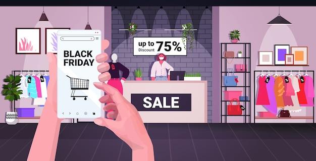 인간의 손에 모바일 앱에서 옷을 구입하는 스마트 폰을 사용하여 검은 금요일 쇼핑 큰 판매 코로나 바이러스 검역 개념 패션 상점 인테리어 수평 벡터 일러스트 레이션