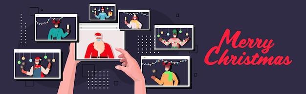 マスクでタブレットpcサンタを使用して人間の手は、ビデオ通話の新年とクリスマス休暇のお祝いの間に混血の人々と話し合うオンライン通信自己分離の概念水平il