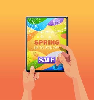 画面の垂直方向の図に春のセールバナーチラシまたはグリーティングカードとタブレットpcを使用して人間の手