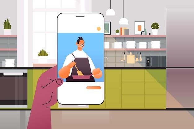 スマートフォンの画面で料理を準備する人間のウォッチングシェフ食品ブロガーオンライン料理コンセプトキッチンインテリアポートレート横図