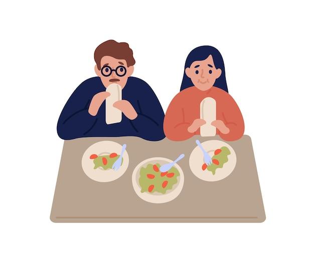 배고픈 부부는 흰색에 고립 된 테이블에 앉아 피타에 팔라 펠을 먹고 프리미엄 벡터