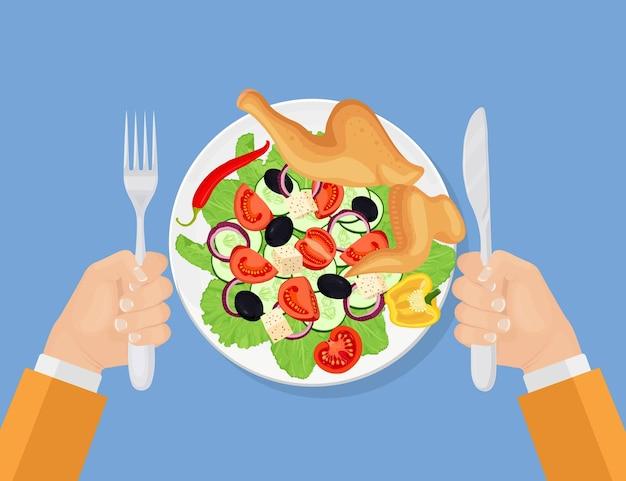 ナイフとフォークを持っている空腹の男。プレートにギリシャ風サラダを添えたグリルチキン。鶏肉、レタスの葉、新鮮な野菜、チーズで作った美味しいレストランの食事。おいしい前菜料理