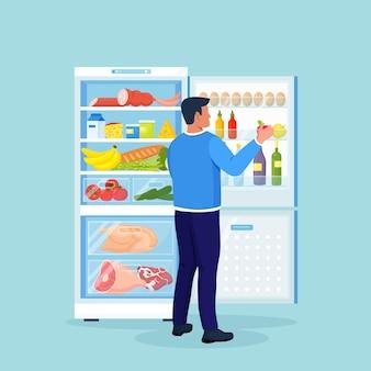 배고프거나 목이 마른 남자는 냉장고 옆에 서서 음식을 선택합니다. 야채, 과일, 고기 및 유제품으로 가득 찬 개방형 냉장고