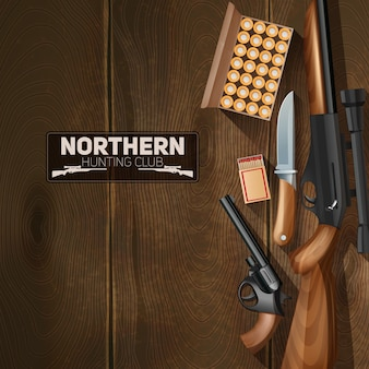 Hunting weapon and bullets set on wooden texture background