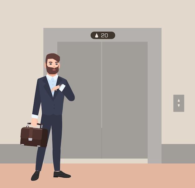 Торопливый бородатый мужчина, бизнесмен или офисный работник, одетый в костюм, стоит перед закрытыми дверями лифта и смотрит на свои наручные часы
