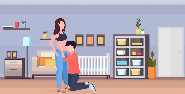 Муж по колено слушает живот беременной жены жизнерадостная семья ждет новорожденного беременность концепция отцовства современные дети bedrooom интерьер горизонтальный полная длина